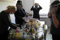 Pracownicy PCPR przy stole, na którym leżą przyłbice